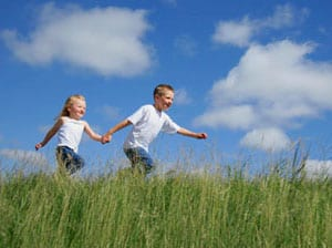 Photo of boy an girl running hand in hand in the grass