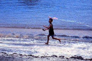 Photo of Brazilian child running with kite along the beach