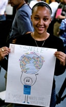 "Link to more info about 9/11/02: Ayaris shows her poster for the 9/11 Anniversary ""Decorate the City"" campaign"