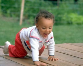 Photo of child crawling on woody floor