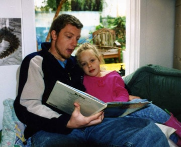Photo of father with daughter reading on book