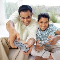 Photo of a man and boy playing video games
