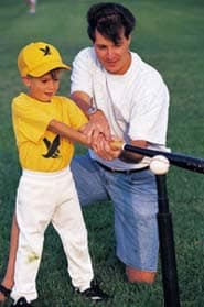 Photo of a man teaching a boy to bat