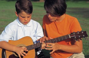 Photo of lady teaching a boy to play guitar