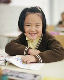 Photo of Chinese girl with smile is sitting at her desk