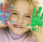 Photo of a girl smiling with paint on her hands