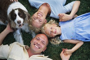 Photo of family with dog on grass